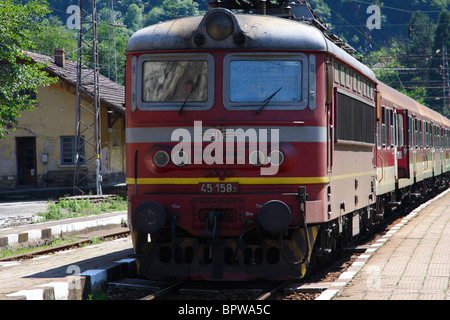 Locomotive and passenger train of the Bulgarian State Railway seen at a station in the Balkan Mountains - Stock Photo