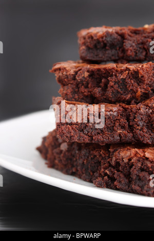 Pile of chocolate fudge brownies on a plate with a grey background (short depth of field) - Stock Photo