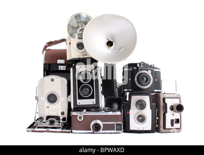 Old antique cameras in a pile on a white background