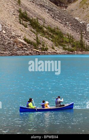 Canoes on beautiful Lake Moraine in Banff National Park, Alberta, Canada. Family enjoying vacation and recreation. - Stock Photo