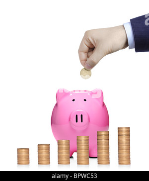 Person inserting a coin into a pink piggy bank with stack of coins in front showing growth - Stock Photo