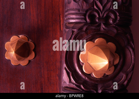 Detail of brass spikes and studs on a beatifully wooden carved door in Stone Tow - Stock Photo