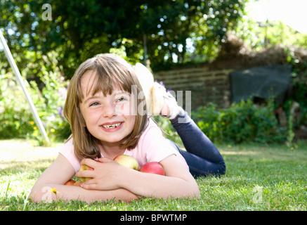 Happy girl in garden with apples - Stock Photo