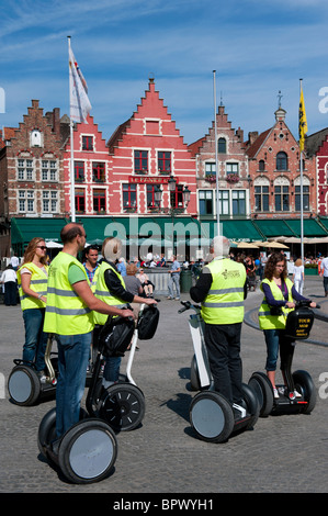 Group of tourists on tour of historic Bruges on Segway electric vehicles in Belgium - Stock Photo