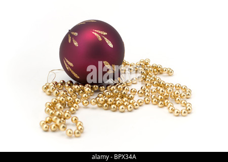 Christmas decorations, a red glass ball and a string of gold beads. - Stock Photo
