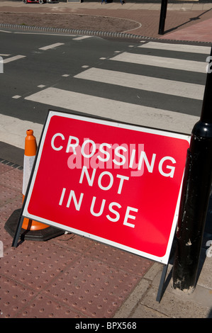 Crossing not in use sign in front of a pedestrian crossing in England. - Stock Photo