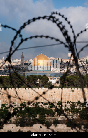 The Old City of Jerusalem, including the Dome of the Rock and various church steeples, seen through coils of razor - Stock Photo