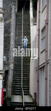 A man walks down the 'Jacob's Ladder' steps in Falmouth, Cornwall - Stock Photo