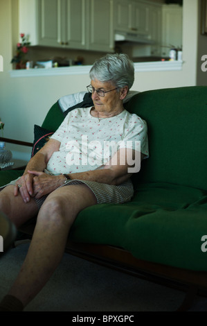 Sad-looking woman sitting on living couch with hands clasped in her lap. - Stock Photo