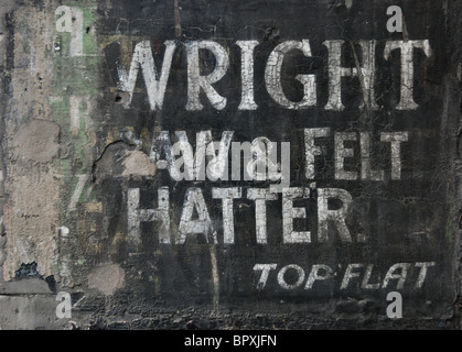 The weathered remains of a painted sign on a wall in Edinburgh's Old Town. - Stock Photo