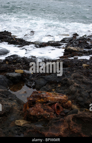 A strange metal object decomposes on the shores of Glass Beach, Hawaii, the former site of a garbage dump. - Stock Photo