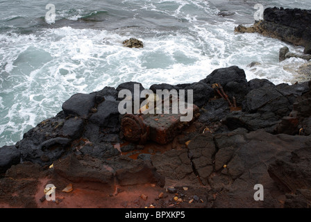 An old, rusted out piece of metallic trash litters the shore of Glass Beach in Hawaii. Glass Beach was a former - Stock Photo