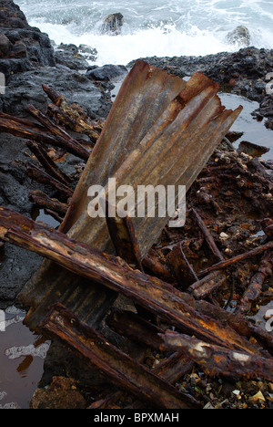 A large rusty metal bit of trash lays rusting on the shores of Glass Beach, Hawaii, the site of a garbage dump decades - Stock Photo