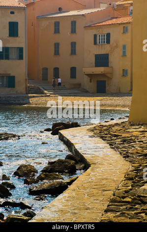 A man and woman walking by the sea wall in St Tropez - Stock Photo