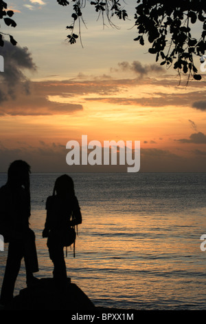 Two local people watch the sunset over the Indian Ocean at Beau Vallon Bay on Mahé in the Seychelles - Stock Photo
