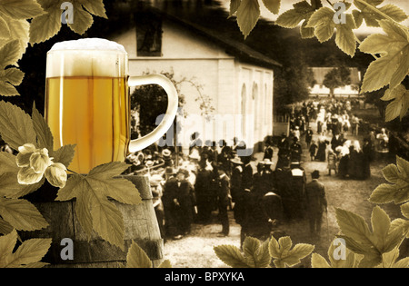 Glass of beer, old barrel and hop plant on background of festive rural scene one hundred years ago - Stock Photo