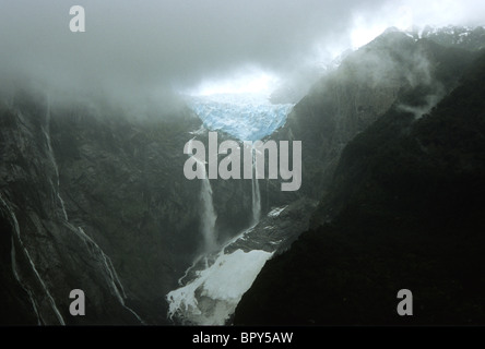 Waterfalls cascade down cliffs from a hanging glacier, Queulat National Park, Southern Chile - Stock Photo