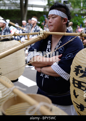 Japanese man carrying lanterns at Akita Kanto Matsuri Lantern Festival - Stock Photo