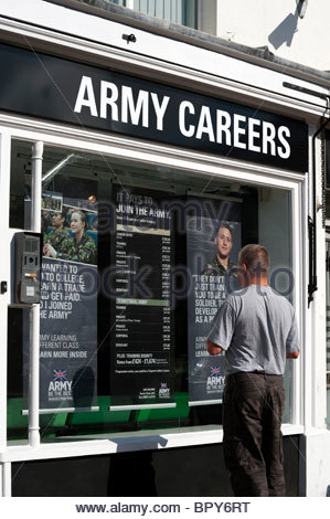 Man looking in the window of an army recruitment office in Commercial Road, Hereford, UK. Army careers office. - Stock Photo