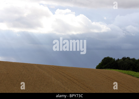 Sun shining through clouds in Oxfordshire - Stock Photo