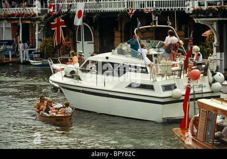 A family risk their safety near a larger cruiser while passing-by in a tiny motorised boat on the River Thames at - Stock Photo