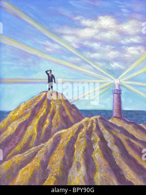 A businessman standing on a peak and looking into the distance, with a lighthouse on another peak - Stock Photo