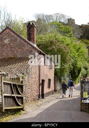 Couple Walking In Dunster Village Exmoor Somerset UK Europe - Stock Photo