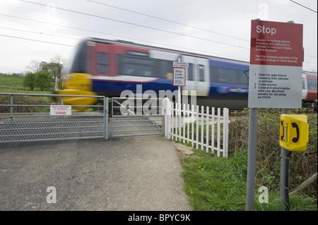 Train going through a pedestrian level crossing. - Stock Photo
