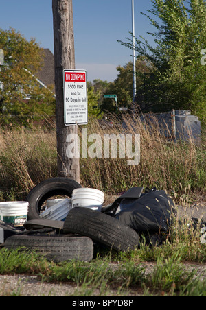 Detroit, Michigan - Old tires and other garbage is dumped in an alley next to a sign warning of penalties for illegal - Stock Photo