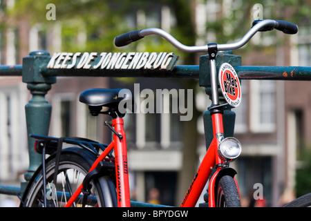 Amsterdam. Rental bike by MacBike leaning against the railing of the Kees de Jongen Canal Bridge in the Jordaan - Stock Photo