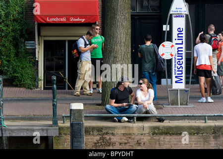 Amsterdam Museum Line Hop On canal cruise tour boat stop in front of the Anne Frank House front door, with people - Stock Photo