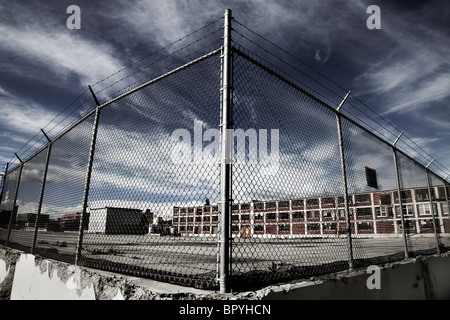A fence in front of a factory building with a dramatic sky. - Stock Photo