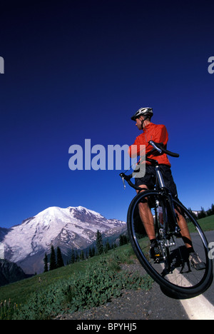 A man takes a break from bike touring to look at the view. - Stock Photo
