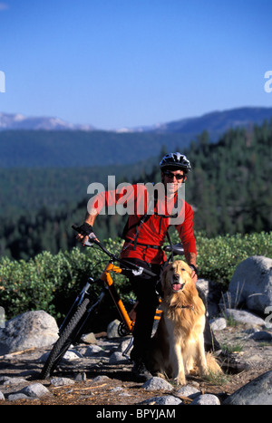 A man takes a break from mountain biking with his dog to look into the camera. - Stock Photo