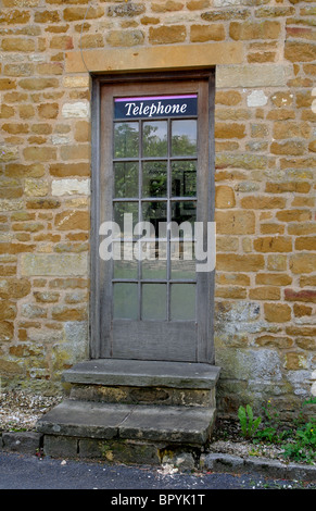 Public telephone kiosk set in a wall, Adlestrop, Gloucestershire, England, UK - Stock Photo