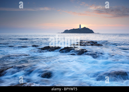 Evening sun setting behind the lighthouse at Godrevy Island - Stock Photo