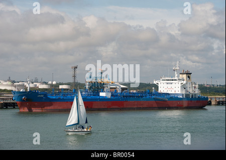 Yacht sailing in front of the crude oil tanker, Jade, at Southampton docks, England. - Stock Photo