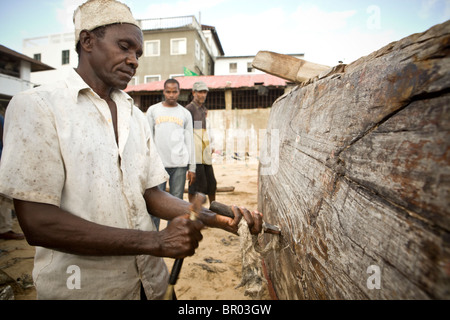 Man repairing a wooden boat in a shipyard - Stonetown, Zanzibar, Tanzania. - Stock Photo