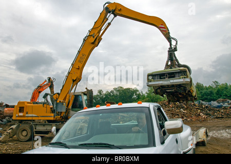Car being unloaded on a pile in a metal scrap yard. - Stock Photo