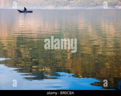 Fisherman in a boat on Lake Atitlan. - Stock Photo