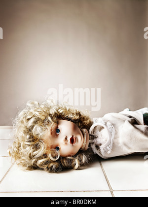 porcelain doll with a broken neck lying on a white tiled floor - Stock Photo