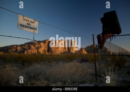 Man wearing a bouldering pad sits on a fence beside a sign. - Stock Photo