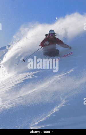 A woman skiing powder snow on a windy day on Donner Summit in California. - Stock Photo