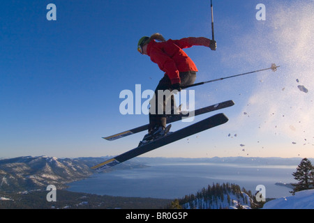 A woman jumping on skis above Lake Tahoe in California. - Stock Photo