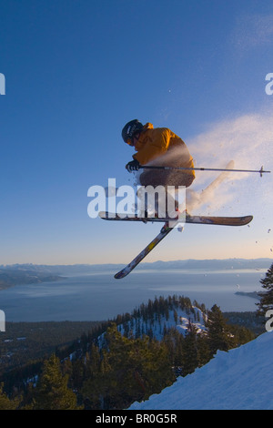 A man jumping on skis above Lake Tahoe in California. - Stock Photo