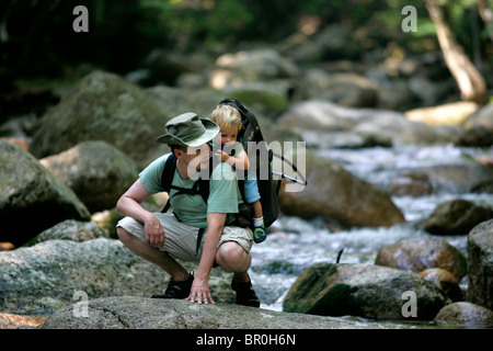 A father hikes with his baby boy along Sabbaday Brook in New Hampshire's  White Mountain National Forest. - Stock Photo