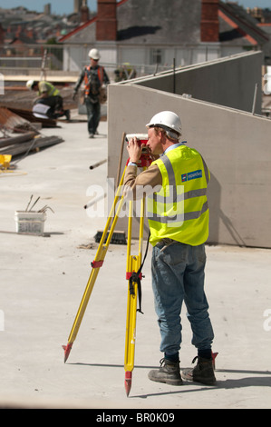 A man, wearing hi vis jacket and full PPE equipment,  working on a building site surveying the location with a Leica - Stock Photo