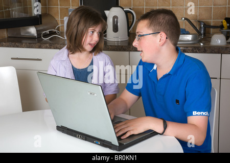 Younger sister helping her brother with his school homework on his laptop computer - Stock Photo