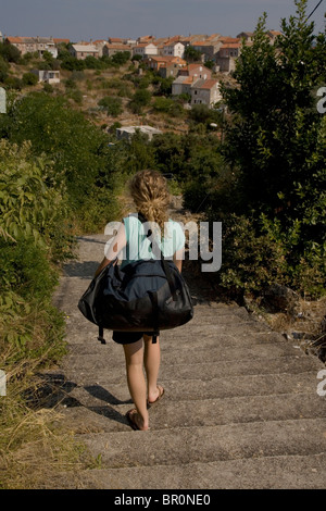 Girl carrying a duffle bag on the remote Island of Iz in Croatia. - Stock Photo