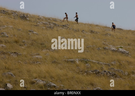 Three people climb a grassy hill on an islands in Kornati National Park in the Adriatic. - Stock Photo